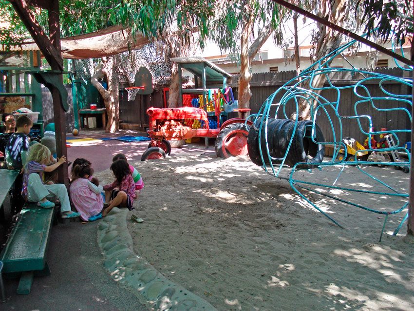 During a Morning Meeting at Play Mountain Place, children gather to look at a sharing.
