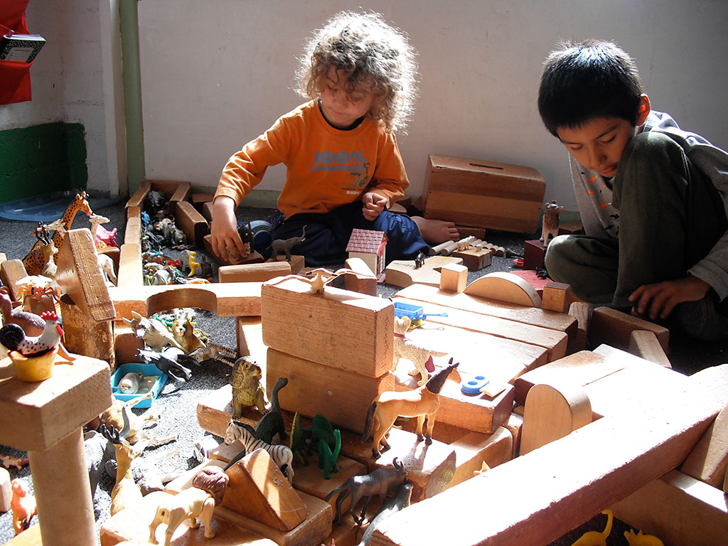 Children build with blocks and place animals in the inside space in the Elementary Program called Mountain House.