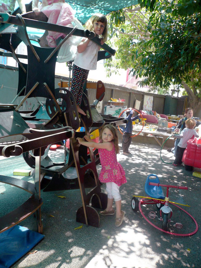 Children climbing on a structure in the Little Nursery yard at Play Mountain Place.